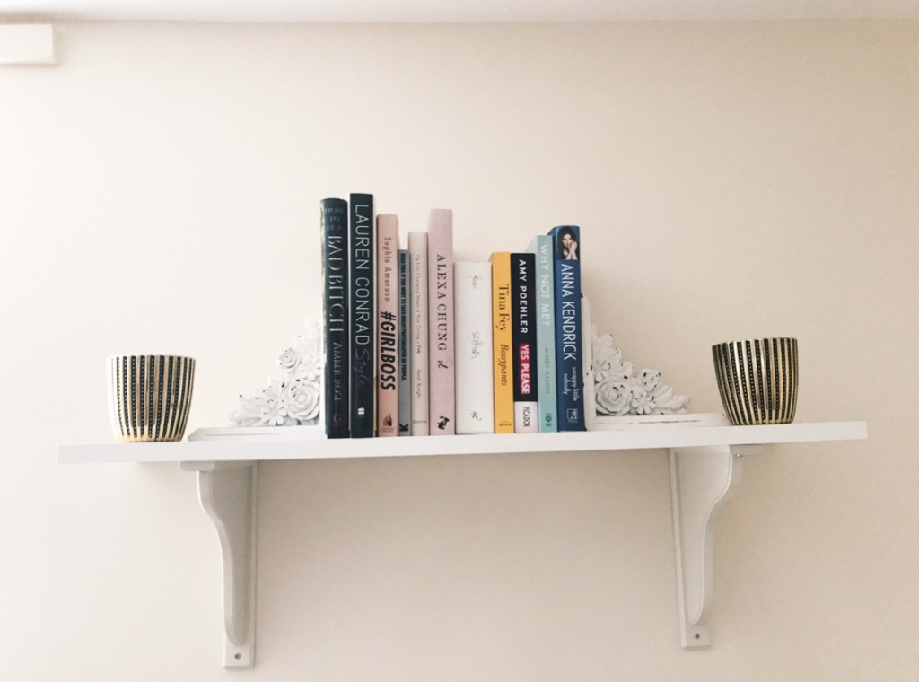 Several non-fiction books are placed on a shelf between white book ends and black and gold candles