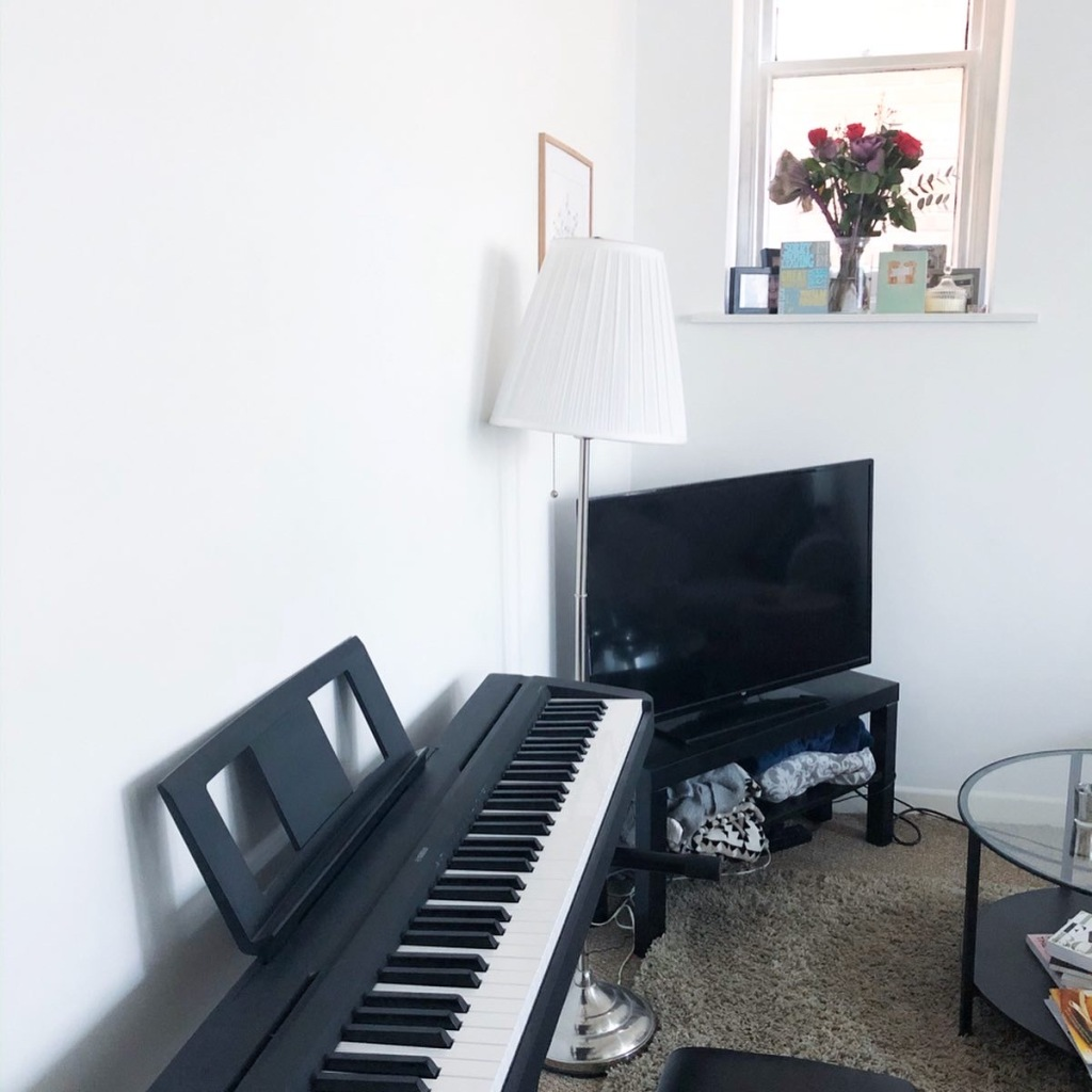 A living room with a black piano sitting in front of lamp and a tv