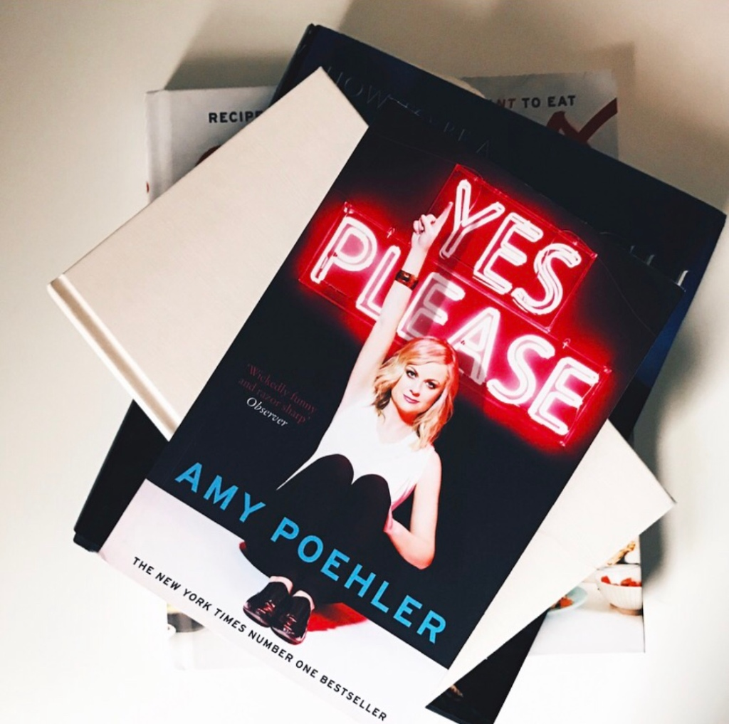 Amy Poehler's non-fiction book 'yes please' is stacked on other books