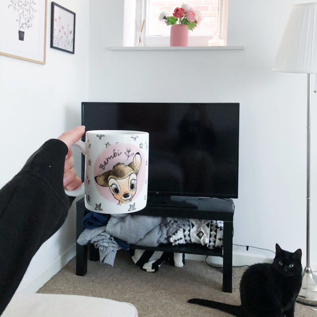 Someone is holding a mug in front a tv whilst a black cat watches on