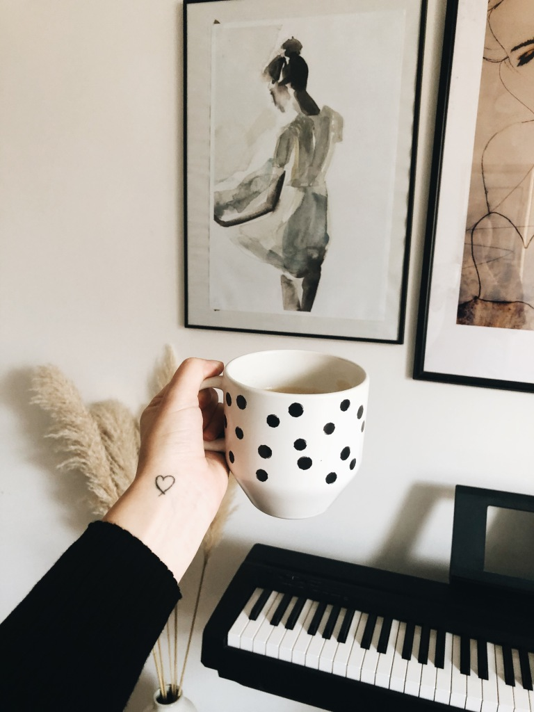 A girl holding a mug in front of an electric piano and pampas grass