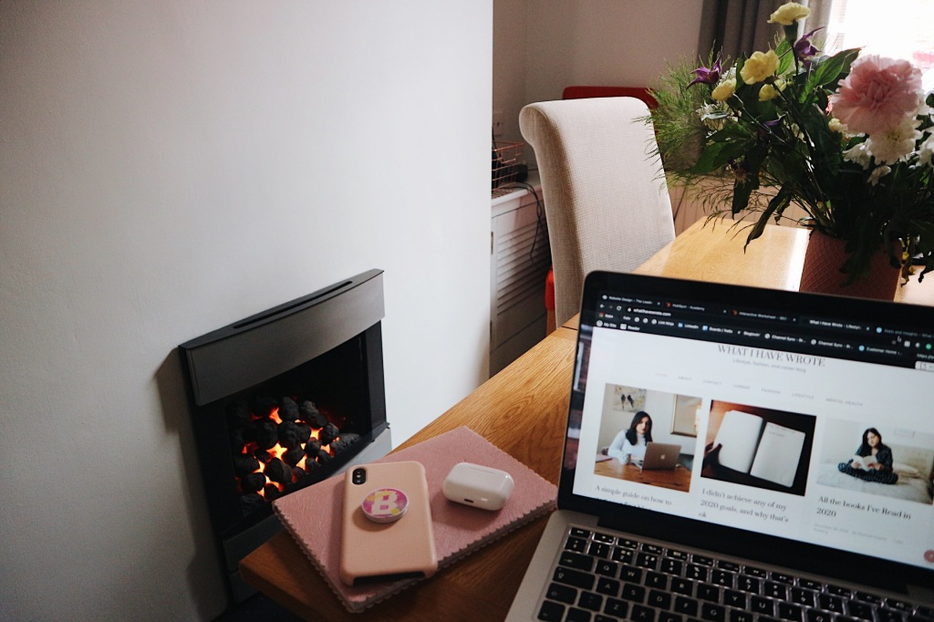 A work from home space with a laptop, a phone and notebook resting on a table with pink and yellow flowers in front of a roaring fire place